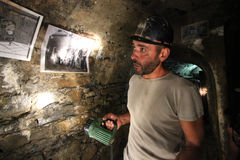 The miners and the mine. A former miner of the mines of Montevecchio in Sardinia explains to visitors the different extraction processes of metals and how is Royalty Free Stock Photo
