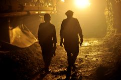 Miners. Two miners heading out from underground after their shift ends, in silhouette Royalty Free Stock Photography