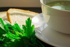 Minestra appetitosa del brodo di pollo su una tavola nera con pane e prezzemolo fotografie stock