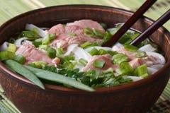 Minestra asiatica con manzo, le tagliatelle di riso e le erbe fresche in una ciotola Immagini Stock Libere da Diritti