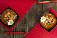 Minestra con i gamberetti in ciotola con i pomodori e le erbe sulla tavola di legno Vista superiore fotografie stock
