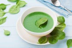 Minestra crema degli spinaci in ciotola sulla tavola rustica blu Immagine Stock