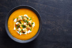 Minestra crema di verdure della zucca con la carota ed i cracker Vista superiore su un fondo creativo scuro Pasto di dieta sana fotografia stock