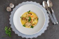 Minestra cremosa con il filetto di pesce e le cozze in un piatto bianco su un panno bianco su un fondo astratto grigio Concetto s Fotografia Stock Libera da Diritti