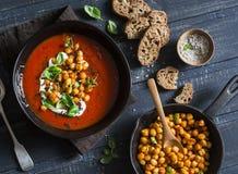 Minestra del pomodoro con i ceci fritti piccanti su una tavola di legno scura, vista superiore Alimento vegetariano sano fotografie stock