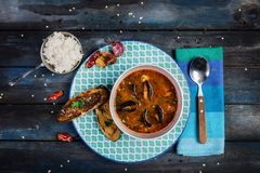 Minestra del pomodoro dei frutti di mare con pane e riso per un contorno su un fondo di legno colorato Vista superiore fotografia stock libera da diritti