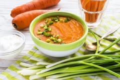 Minestra del purè della carota con panna acida e la cipolla verde Fotografie Stock