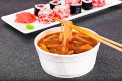 Minestra del WOK - tagliatelle di riso, tofu, basato a pomodoro e sushi fotografia stock libera da diritti