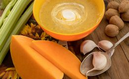 Minestra della carota e della zucca con crema e prezzemolo sulla tavola di legno scura con il selery, il garlick ed i pezzi di zu fotografie stock