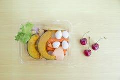 Minestra della zucca, patate bollite, uova in una scatola di plastica, frutta della ciliegia, angolo superiore immagini stock libere da diritti