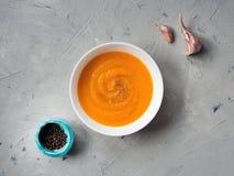 Minestra della zucca, vista superiore, spazio della copia Alimento stagionale di autunno - minestra piccante della zucca con agli immagini stock