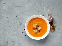 Minestra della zucca, vista superiore, spazio della copia Alimento stagionale di autunno - minestra piccante della zucca con i cr fotografia stock
