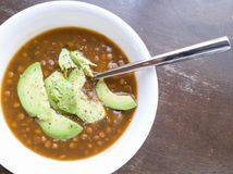 Minestra di lenticchia con l'avocado in ciotola bianca con il cucchiaio Immagini Stock