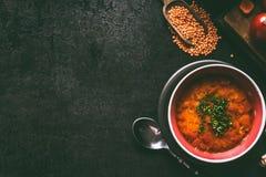 Minestra di lenticchia rossa con il cucchiaio in ciotola su fondo rustico scuro, vista superiore con lo spazio della copia Alimen fotografia stock libera da diritti