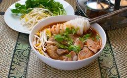 Minestra di pasta piccante asiatica con la tenuta del bastoncino sulla tagliatella con carne di maiale fotografia stock libera da diritti