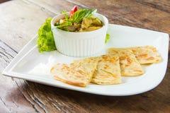 Minestra di pollo rossa del curry servita con il roti Immagini Stock