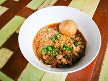 Minestra di tagliatelle tailandese dei vermicelli del riso con manzo ed una grande palla del manzo in ciotola bianca sulla tavola immagini stock