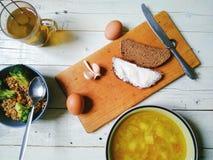 minestra di verdura, una ciotola di porridge del grano saraceno, pane e burro, uova, una tazza di tè ed aglio sulla tavola Fotografia Stock Libera da Diritti