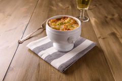 Minestra francese della cipolla su una tavola di legno con un vetro di vino bianco immagini stock libere da diritti