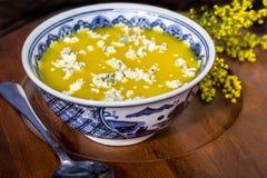 Minestra gialla con la guarnizione del formaggio blu Immagini Stock