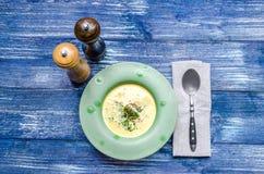 Minestra gialla del formaggio con carne e le erbe, in un piatto verde, con un cucchiaio e le spezie su un fondo blu del denim Immagini Stock Libere da Diritti