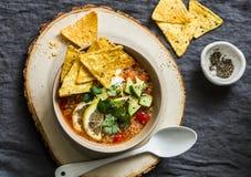 Minestra vegetariana del pomodoro della quinoa con le patatine fritte, l'avocado ed il coriandolo del formaggio del cereale su fo immagine stock