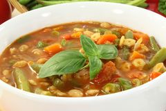 Minestrone. A bowl of minestrone soup and basil Stock Photos