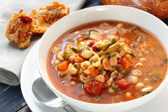 Minestrone. Bowl of minestrone with fresh bread baked with sundried tomatoes Royalty Free Stock Photography