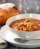 Minestrone. Pasta soup on rustic table, with fresh-baked cob of bread Stock Image