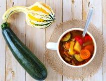 Minestrone på träbakgrunden med pumpa och zucchinin Royaltyfri Foto