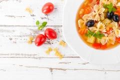 Minestrone, sopa do vegetariano com massa e vegetais no fundo rústico de madeira branco Alimento italiano tradicional fotos de stock royalty free