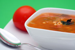Minestrone soup. Italian vegetable soup called minestrone in a white bowl with fresh tomato as decoration Royalty Free Stock Image