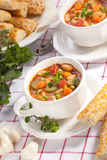 Minestrone soup. Two bowls of hot fresh Minestrone soup and cheese garlic breadsticks Stock Photography