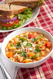 Minestrone soup. Closeup of bowl of hot fresh Minestrone soup and whole wheat bread turkey breast sandwich Stock Images