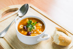 Minestrone Soup. Bowl of minestrone soup garnished with fresh parsley and with baguette and silver spoon aside closeup Stock Images