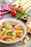 Minestrone soup. Vegetable soup with fresh tomato, celery, carrot, zucchini, onion, pepper, beans and pasta. Dish of italian cuisi Stock Image