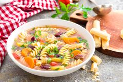 Minestrone soup. Vegetable soup with fresh tomato, celery, carrot, zucchini, onion, pepper, beans and pasta. Dish of italian cuisi Royalty Free Stock Photo