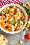 Minestrone soup. Vegetable soup with fresh tomato, celery, carrot, zucchini, onion, pepper, beans and pasta. Dish of italian cuisi. Ne. Top view royalty free stock photo