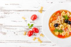 Minestrone, vegetarian soup with pasta and vegetables on white wooden rustic background. Traditional italian food. Top view royalty free stock photos