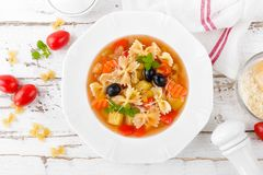 Minestrone, vegetarian soup with pasta and vegetables on white wooden rustic background. Traditional italian food. Top view royalty free stock photography