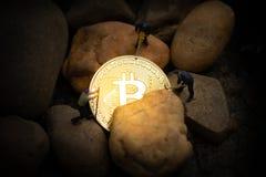 Mineurs miniatures creusant le bitcoin d'or dans le mien photographie stock
