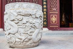 Ming Dynasty Stone Urn. A giant Ming Dynasty stone urn with a double dragon motif adorns the entrance way to a prayer room Royalty Free Stock Photos