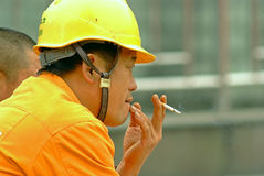 Mingshan China-A worker is smoking Royalty Free Stock Photography