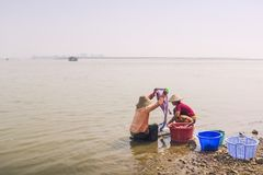 Mingun , Myanmar - Feb 18,2018 : Burmese female washing her clothes in the Irrawaddy river stock photo