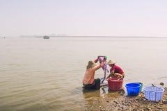 Mingun, Myanmar - febbraio 18,2018: Femmina birmana che lava i suoi vestiti nel fiume di Irrawaddy fotografia stock
