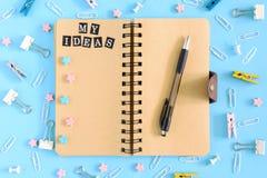 Minhas ideias Bloco de notas nas molas com páginas marrons em um fundo azul Os materiais de escritório são dispersados caoticamen imagem de stock