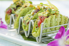 Mini Ahi Poke Tacos. Ahi poke tacos with avocado mousse, island salsa, bubu arare in a mini shell Stock Photos