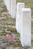 Mini American flagg faps in de wind dichtbij een graf Stock Fotografie