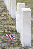 Mini American flaggfaps i vinden nära en grav Arkivbild