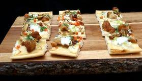 Mini aperitivi della pizza sul tagliere di legno Immagine Stock